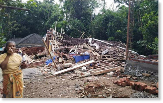 A resident of Montong Gading district, East Lombok, stands by her collapsed house after an earthquake on Sunday