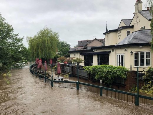 Flooding sweeps the beer garden at the Alyn Riverside Country Pub in Rossett, North Wales