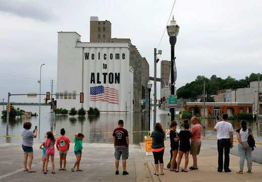 People gather in downtown Alton, Ill. on Saturday as the Mississippi River there reached a level of 39 feet