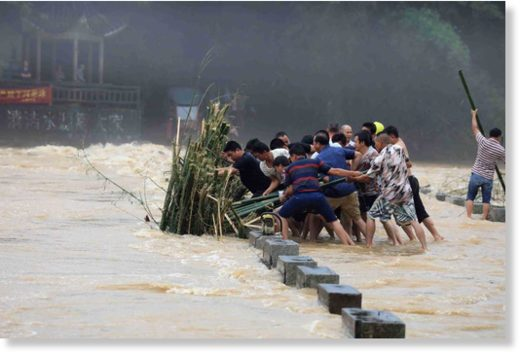 Disaster relief personnel and villagers work together to remove debris stuck near a bridge amid flooding in Liuzhou