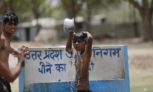 Indian boys bath at a drinking water tap on a hot day in Prayagraj, India