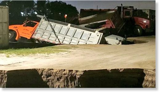 Trucks can be seen sticking out of a possible sinkhole in Florida early Wednesday.