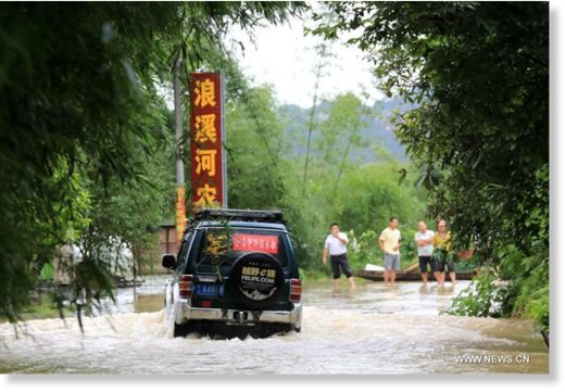 A vehicle runs in the flooded areas in Chang'an Town, Rong'an County, south China's Guangxi Zhuang Autonomous Region, July 9, 2019.