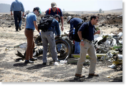 American civil aviation and Boeing investigators searching through the debris