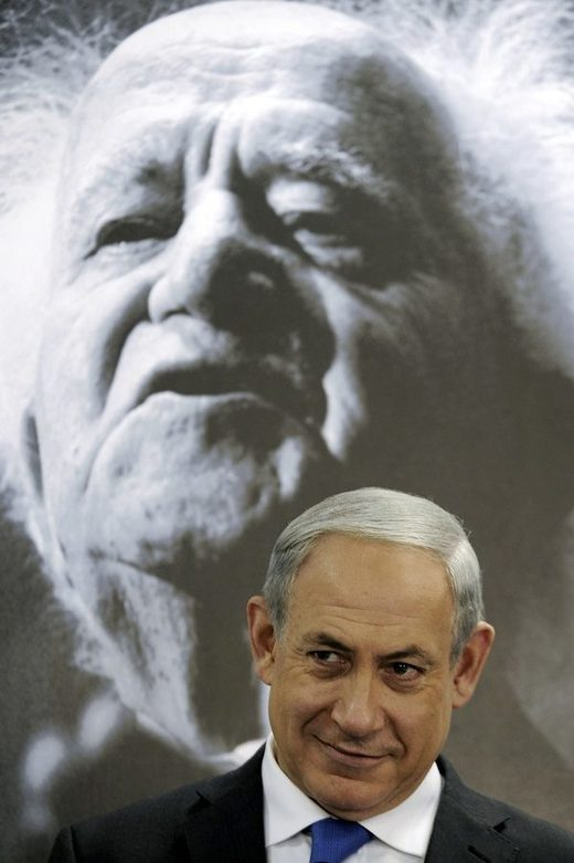 Benjamin Netanyahu sits in front of a picture of David Ben-Gurion