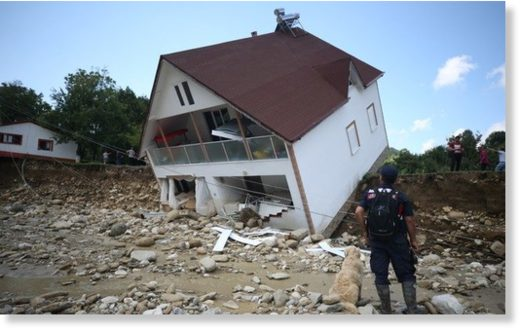 A gendarmerie personnel looks at a house tipped over due to floods in Esmahanım village, Düzce, July 19, 2019.