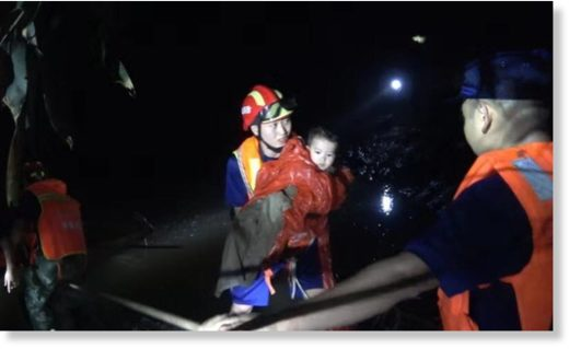Rescuers pull tourists out of the flood which hit Duobi Gorge at Hefeng county in Hubei province on Sunday night.