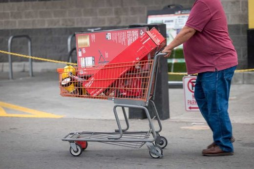 A customer pushes a shopping cart with batteries and flashlights