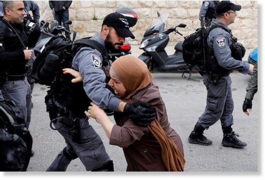 An Israeli policeman pushes back a Palestinian woman