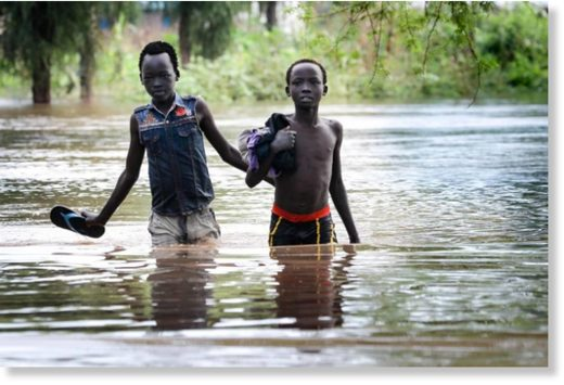 Two boys pick their way along a flooded road in Maban county, South Sudan.