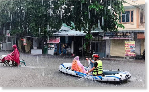 People travel on a flooded street in Vinh, Nghe An Province, October 17, 2019.