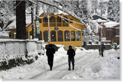 People walk on a snow-covered road during the first snowfall of the season in Gulmarg. Kashmir witnessed its first snowfall of the season, plunging the mercury to sub-zero in Gulmarg and bringing woes galore.