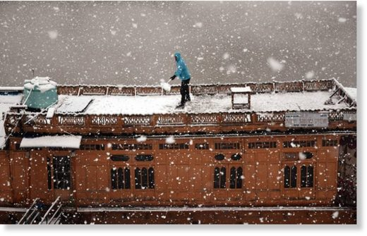 A boatman clears snow from his boat during the first snowfall in Srinagar