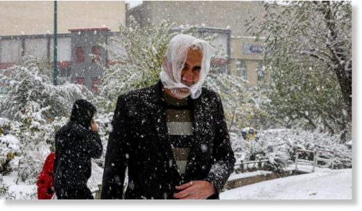People walk under heavy snow in the Iranian capital Tehran on November 16, 2019.