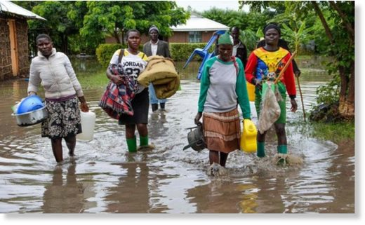 Displaced families flee to higher ground in K'akola village in Nyando sub-county in Kisumu, Kenya, after their houses were flooded on December 3, 2019
