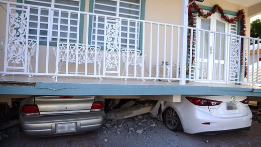 Cars were crushed under a home in Guanica that collapsed after Monday's earthquake