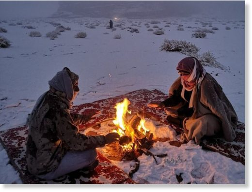 Two men camp out by a fire in Tabuk during the snow.
