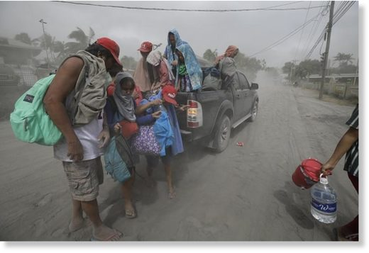 A family evacuates to safer grounds as Taal Volano continues to spew ash in Lemery, Batangas, southern Philippines on Monday Jan. 13, 2020.