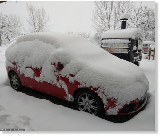 A car is pictured covered in snow after stormy weather hit Albacete in Castilla La Mancha, Spain