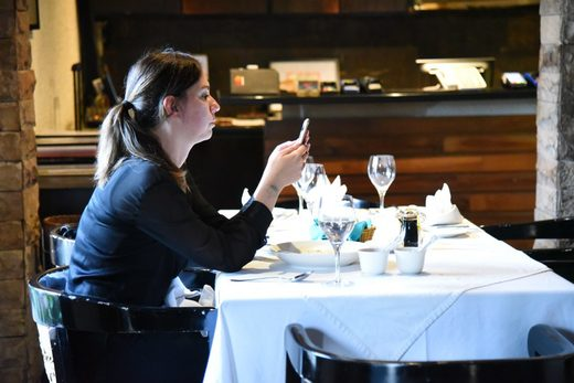 woman dining alone texting phone