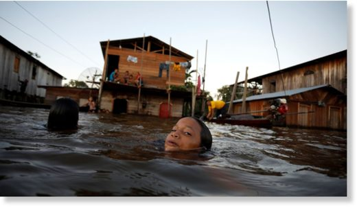 A child swims through a flooded street in Anama, Amazonas state