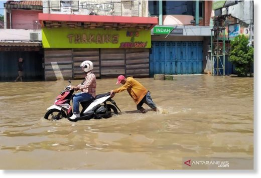 A motorcyclist attempted to pass by a flood-hit road in Dayeuhkolot area of Bandung District, West Java.