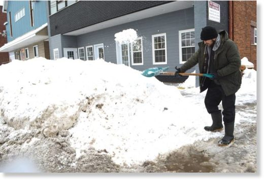Nathan Quinn of Alder Point clears the sidewalk in front of J. Francis Investments on George Street, Sydney, Friday. A record 179.8 cm of snow was registered at the Sydney airport in January, the most since records have been kept dating back to 1870.
