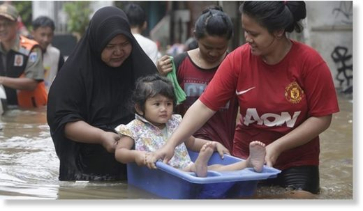 Residents carry a young girl as they walk in a flooded street in Jakarta, Indonesia