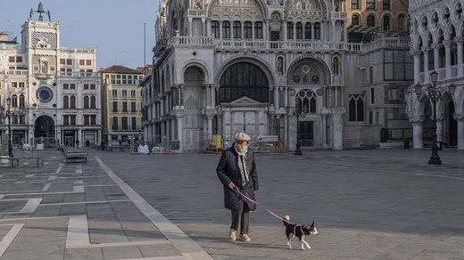 An elderly person walks his dog