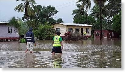 Rescue workers make their way through a village during flooding caused by the Tropical Cyclone Harold in Nasolo in Fiji