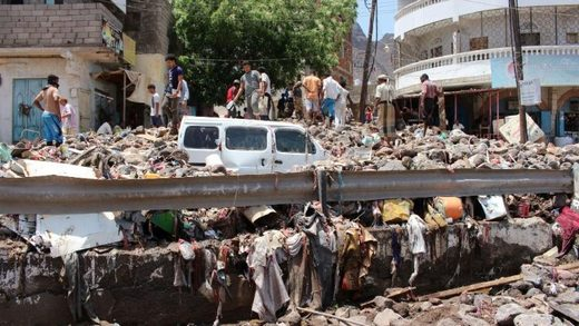 People inspect damage caused by floods on a street in Aden, Yemen
