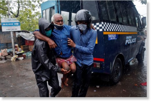 Police officers carry a disabled man to a safer place following his evacuation from a slum area before Cyclone Amphan makes its landfall, in Kolkata, India, on May 20, 2020.