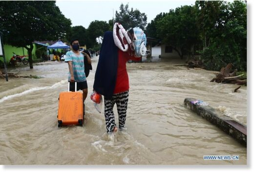 Residents wade through flood water