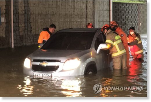 Firefighters help a driver on a flooded road in  in this photo provided by the Incheon Metropolitan Fire and Disaster Headquarters, as heavy rains pounded most of the country.