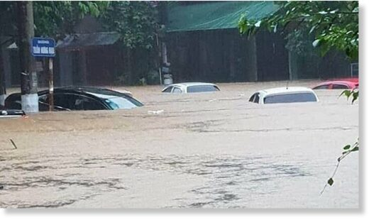 Flooding almost bury cars on a street in Ha Giang