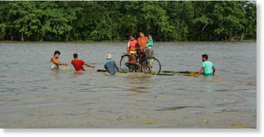 Villagers on a banana raft move to a safer place from the flooded area of Goalbil in Baksa district of Assam.