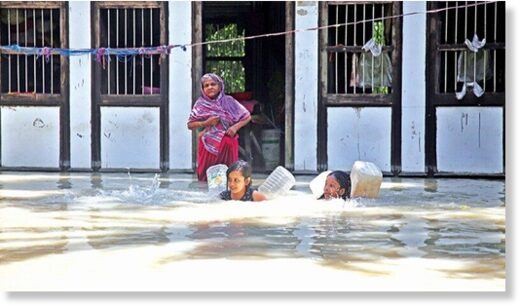 Two children swim to fetch fresh water as a woman looks on in a flood-hit area of Lauhajang upazila in Munshiganj on Tuesday.