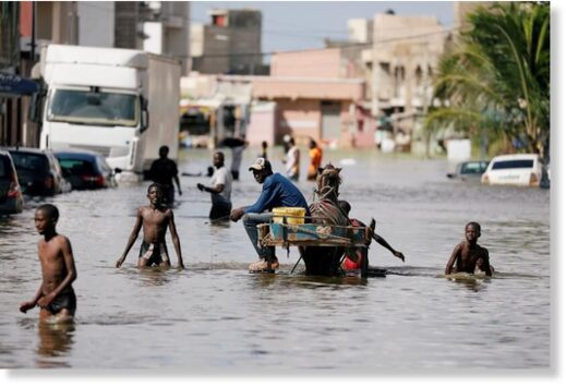 Residents walk through a flooded street after last week's heavy rains in Keur Massar, Senegal September 8, 2020.