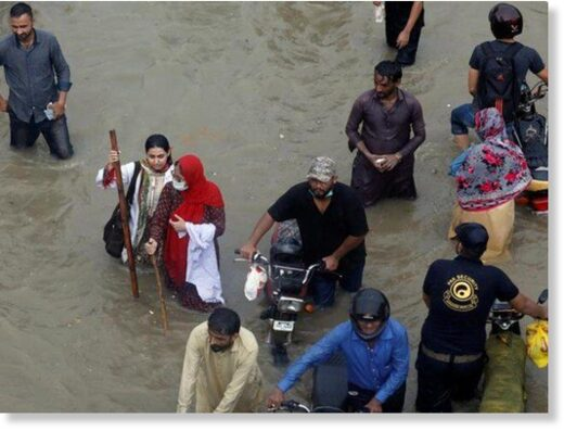 People wade through a flooded road during monsoon rain in Karachi, Pakistan.