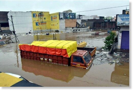 Vehicles lie partially submerged in floodwater following heavy rains, at Falaknuma, in Hyderabad.