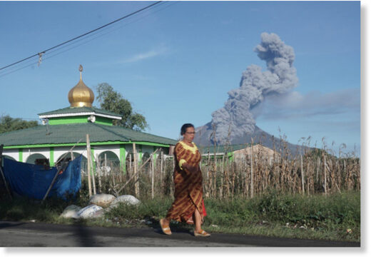 A woman walks as Mount Sinabung spews