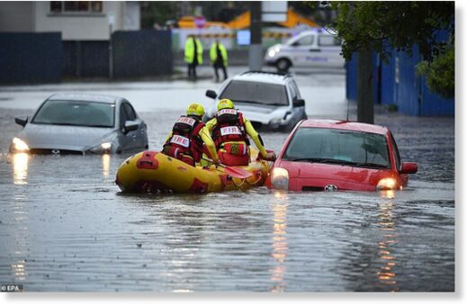 Members of the Swift Water Rescue team from the Queensland Fire and Emergency Services were seen searching flooded cars on Longlands Street at Woolloongabba in Brisbane on Tuesday afternoon