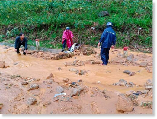 Two men on motorbikes were buried under mud and rocks on Truong Son Dong Street before being rescued.
