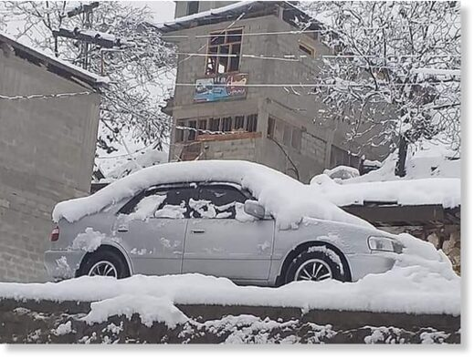 A car covered in snow appear stuck in what seems to be at least two feet of snow on a street in Lower Dir