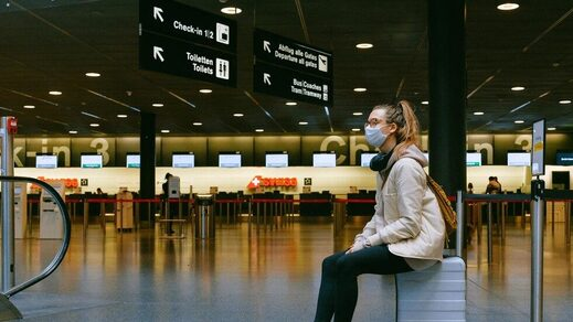 woman sitting airport with mask