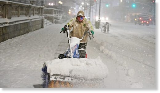 A man clears snow as snow falls near Bryant park in Manhattan, New York City Wednesday.