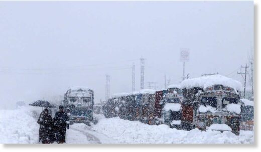 People walk past stranded vehicles on the Jammu-Srinagar National Highway during heavy snowfall, at Qazigund in Anantnag district of South Kashmir on January 5.(PTI)