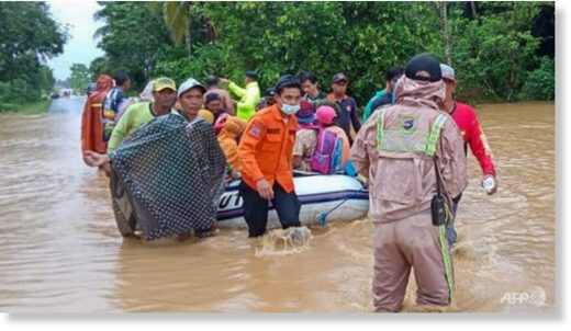January 15, 2021, by the Indonesian National Board for Disaster Management (BNPB) shows rescuers evacuating villagers by rubber boat in a flooded area in the Tanah Laut districts, South Kalimantan.