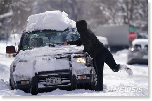 A Denver motorist works to clear