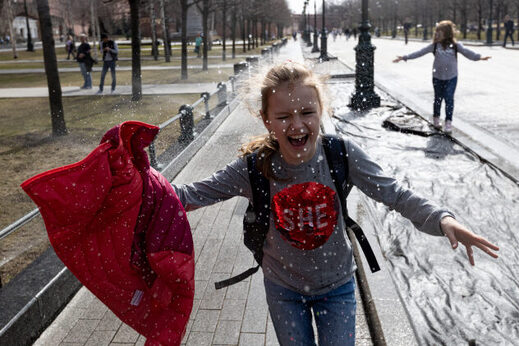 A girl runs through a watering fountain cooling herself during a warm day near the Kremlin Wall in Moscow, Russia